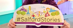 Woman holding a sign that reads #SalfordStories